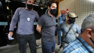 De camisa polo, bermuda e máscara, o vereador Doutor Jairinho é conduzido por policial; ele está algemado, mas suas mãos, posicionadas nas costas, não aparecem na imagem