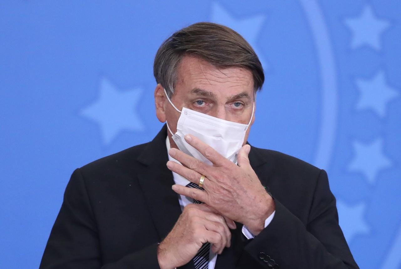 Presidente Jair Bolsonaro colocando uma máscara no rosto