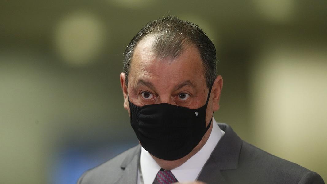 Imagem mostra o senado Omar Aziz, um homem calvo e de olhos pretos, com um paletó cinza, camisa branca, gravata chumbo e e máscara preta