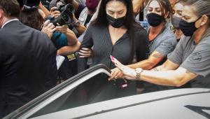 Cercada por policiais e fotógrafos, Monique Medeiros, mãe de Henry, entra no carro da polícia