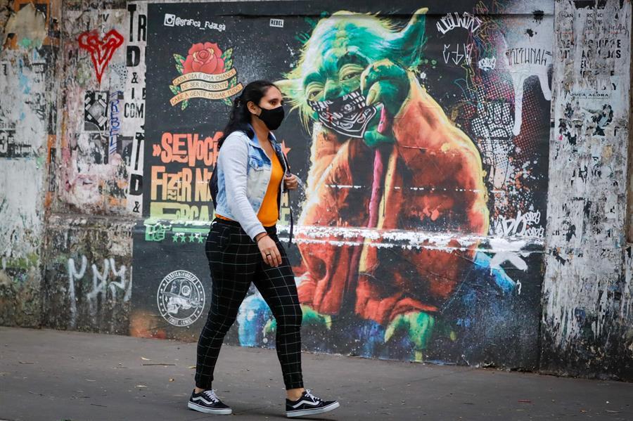 Mulher de máscara caminha em frente a muro grafitado