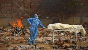 Enfermeiro paramentado ao lado de corpo de homem morto