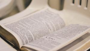 Bíblia aberta em cima de uma cadeira branca