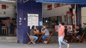 pessoas sentadas em comércio na rua