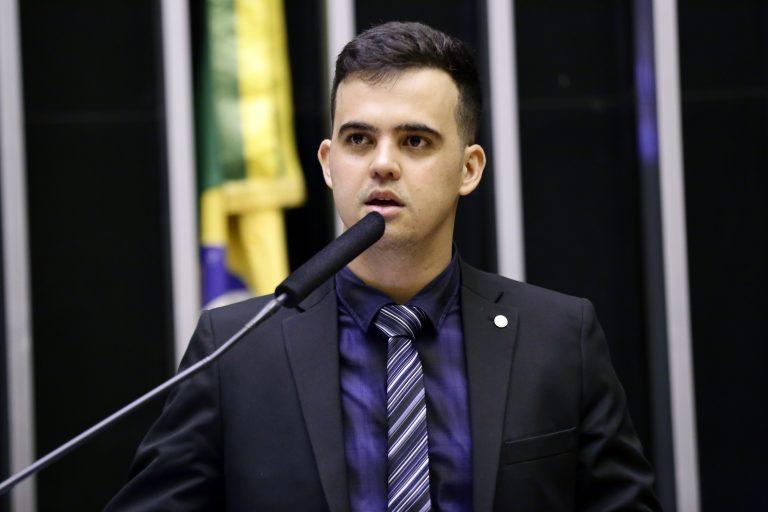 homem de terno e gravata falando em microfone