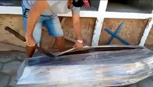homem usando facão para abrir caixão