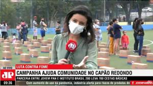 Repórter Carolina Abelin fala do Capão Redondo; no fundo, pessoas fazem fila para receber cesta básica