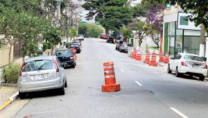 carros parados na rua em asfalto com vários cones laranjas