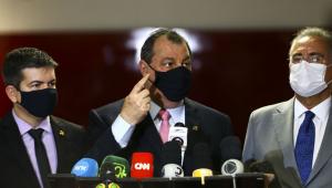 Três homens brancos juntos falando em coletiva de imprensa, com microfones apoiados em um palanque. Os três usam máscara de proteção preta e o do meio está com o dedo levantado.