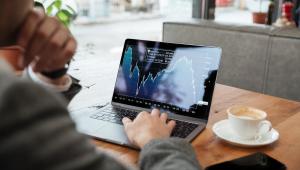 Homem sentado em uma mesa de um café analisa investimentos em seu computador