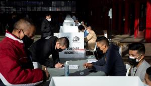 pessoas votando em urna de papel