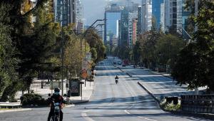 Motorista circula por uma avenida quase vazia em Santiago do Chile