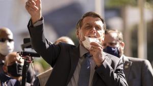 Com a máscara no queixo e a mão direita apontada para cima, em sinal de arma, Jair Bolsonaro caminha em Chapecó