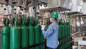 Homem mexendo nos cilindros de oxigênio