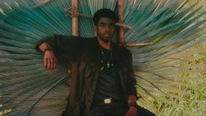 Vestido como soldado americano no Vietnã, o ator Chadwick Boseman posa em cenário que lembra a selva do país asiático