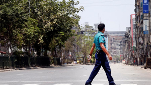 Policial atravessa rua em Dhaka, Bangladesh