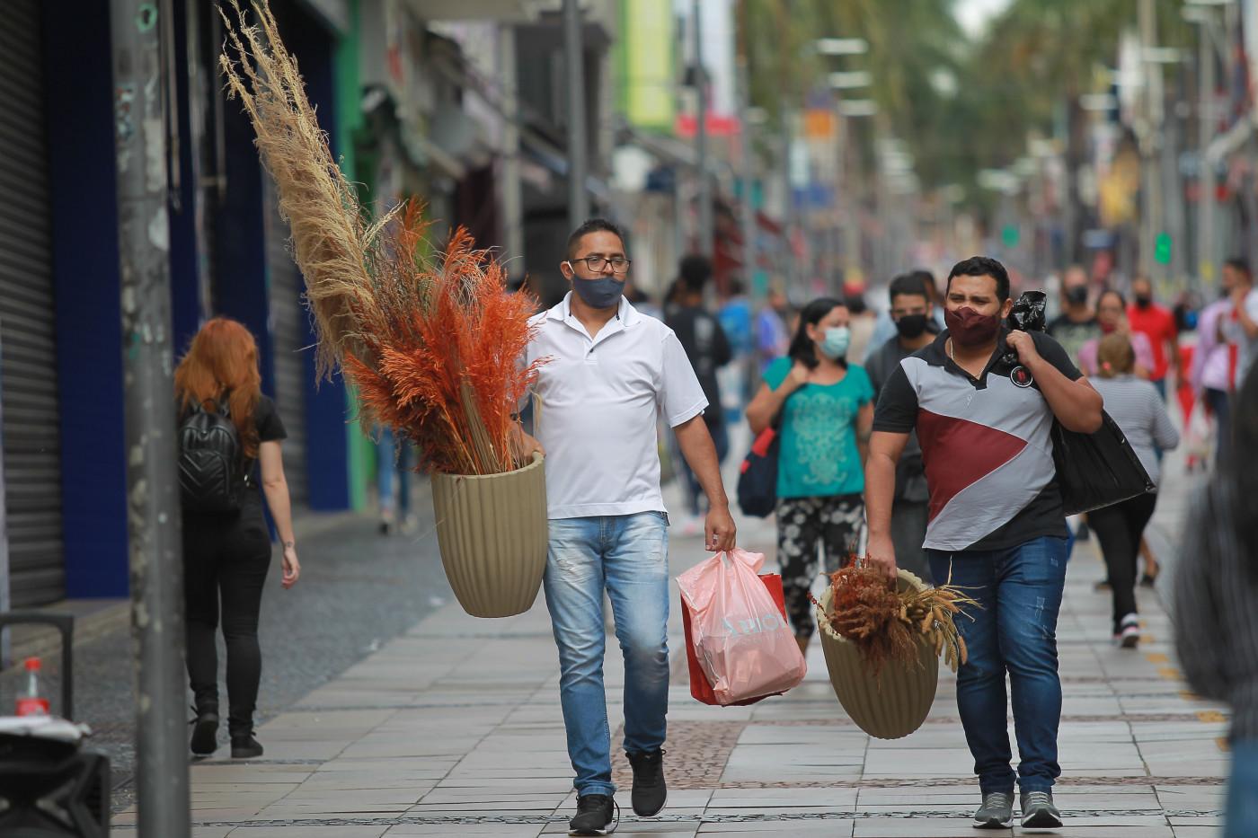 Pessoas caminham na rua com sacos de compra nas mãos