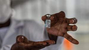 Enfermeira mostrando frasco da vacina CoronaVac
