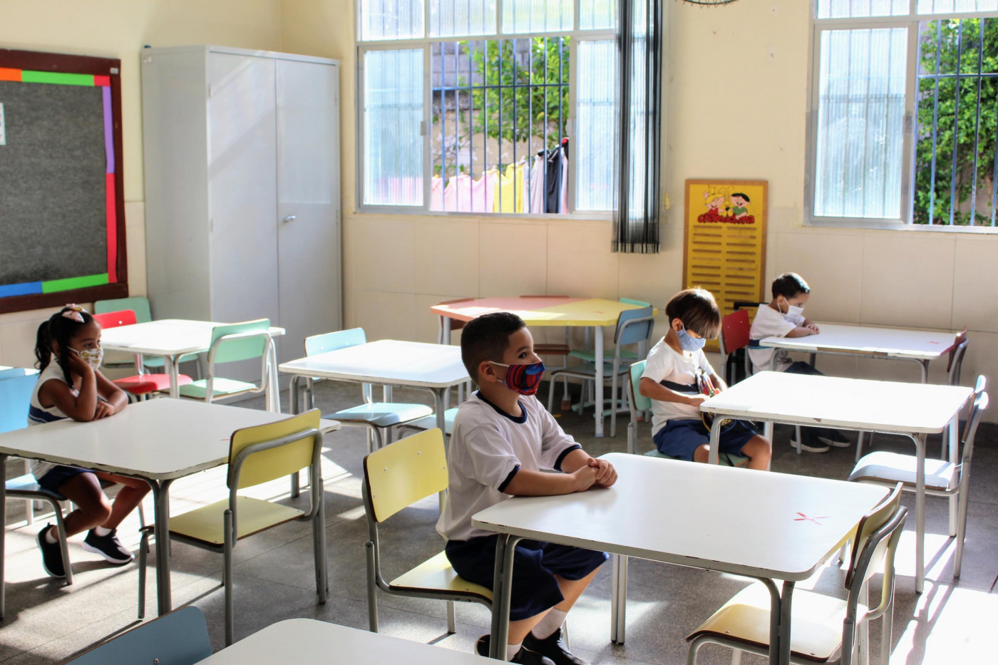 Quatro crianças sentadas na carteira escolar, uma distante da outra, assistem a uma aula em escola do Rio de Janeiro