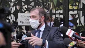 homem de máscara branca dando entrevista para vários microfones