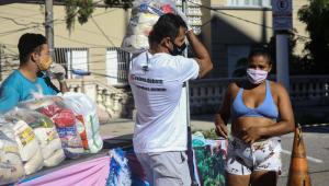pessoa carregando uma sacola com cesta básica no ombro