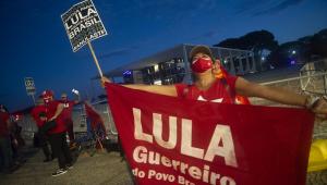 """De boné vermelho e camiseta do PT, umamanifestante segura faixa com a mensagem """"Lula, guerreiro do povo brasileiro"""" em frente ao STF"""