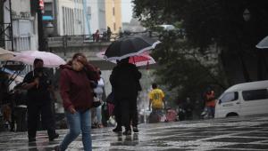 Pedestres se protegem da chuva que cai na região central de São Paulo (SP), nesta quinta-feira