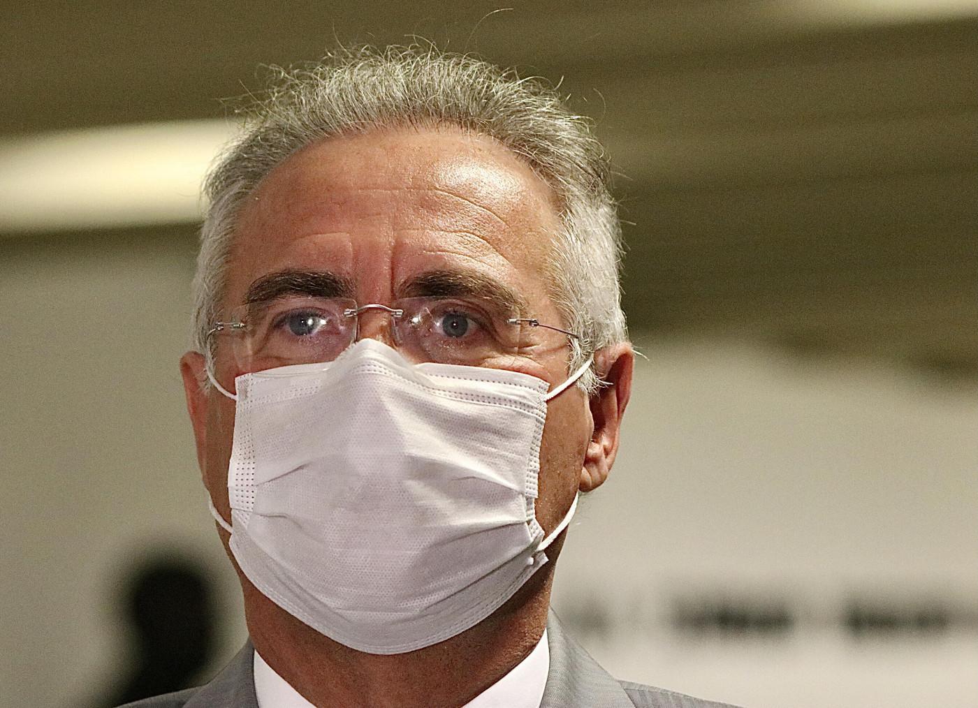 Senador Renan Calheiros usando máscara de proteção branca. Homem com cabelos grisalhos, pele branca e óculos transparentes.