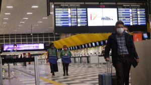 Homem de mala e máscara andando no aeroporto de Congonhas