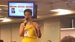Mulher de cabelo curto, vestido amarelo e crachá falando em microfone