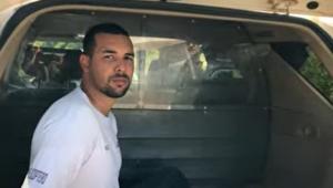 Homem sentado com os braços para trás no porta-malas de um carro