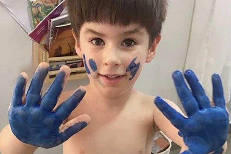 Criança com mão pintada de azul