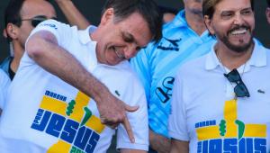 Vestindo uma camiseta brancacom Jesus escrito em azul, Jair Bolsonaro, ao lado de homem com a mesma roupa, olha para o chão e faz sinal de arma com a mão