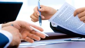 Imagem mostra as mãos de duas pessoas sobre uma mesa, sendo que ambas seguram uma caneta, mas apenas uma maneja um contrato
