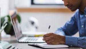 homem escrevendo em uma folha de papel branca em cima de uma mesa com um notebook aberto