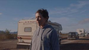 Cena do filme Nomadland em que Fern (Fraces McDormand) aparece atrás de um trailer na estrada