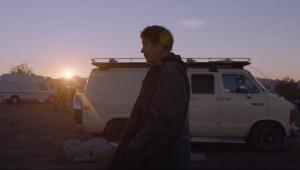 """Fern, personagem de Frances McDormand em """"Nomadland"""", aparece em pé, com casaco pesado, em um camping para trailer"""