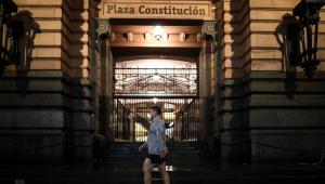 Homem de bermuda, casaco e máscara caminha em uma calçada de Buenos Aires