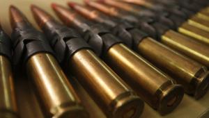 Uma série de balas de metralhadora apreendidas pela polícia são dispostas lado a lado em uma mesa