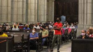 Pessoas acompanham missa sentadas em bancos; uma pessoa em pé