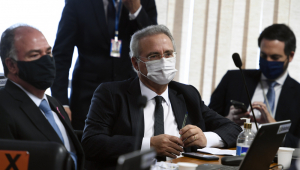 Sentado em sua mesa com uma máscara branca e segurando uma caneta na mão esquerda, o senador Renan Calheiros aparece entre dois colegas