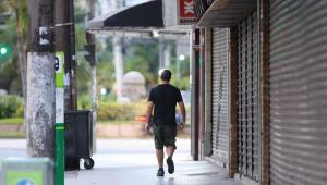 Com comércios fechados ao redor, Homem anda em calçada de Santos