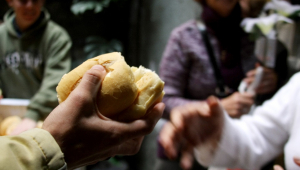 pessoa distribuindo um pedaço de pão