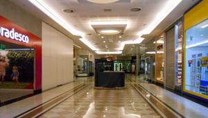 Corredor de shopping center vazio, com lojas ao redor fechadas