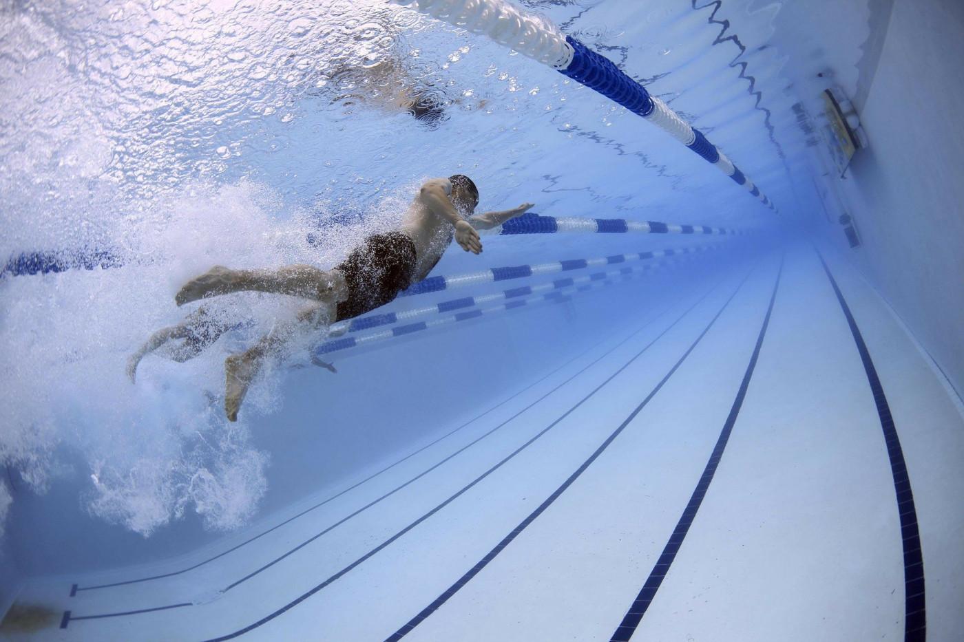 Homem fazendo natação em raia de piscina olímpica