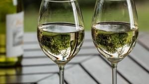 Duas taças com vinho branco servido até a metade apoiadas em uma mesa de madeira, que está em segundo plano