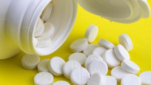 pote de remédios aberto com comprimidos no chão