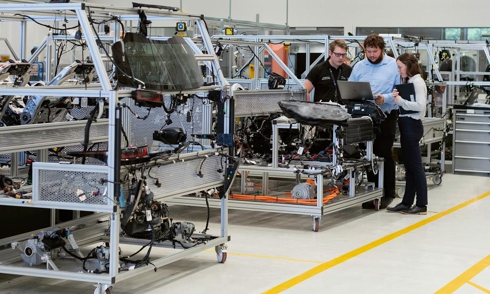 Cercados por peças metálicas guardadas em stands, dois homens e uma mulher olham a tela de um computador em uma ala de uma fábrica de carros