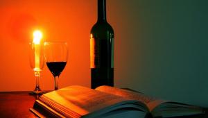 garrafa de vinho, taça com meio copo cheio e livro. vela acesa