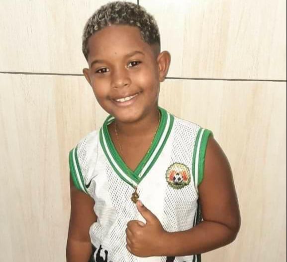 Menino de camiseta branca e verde sorrindo